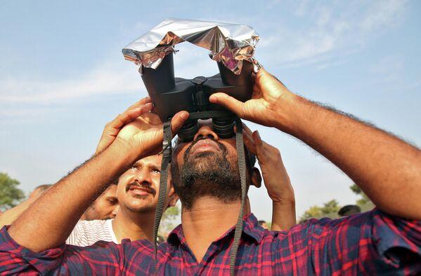 Мужчина использует бинокль покрытый пленкой, чтобы наблюдать кольцевое солнечное затмение в городе Черуватур, Индия