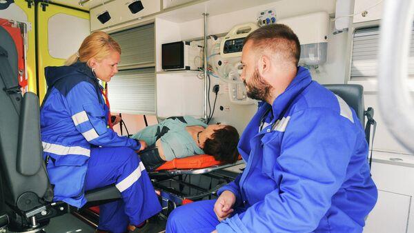 Врачи бригады скорой медицинской помощи оказывают первую помощь пациенту в салоне реанимобиля