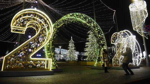 Прохожие фотографируются у световой иллюминации на Лубянской площади в Москве