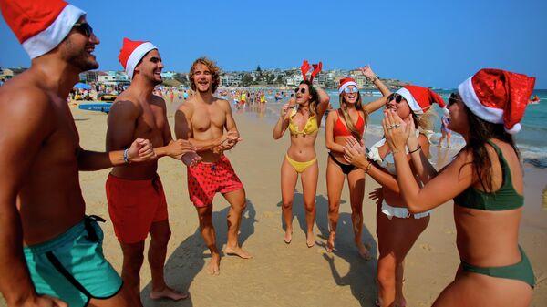 Туристы в рождественских костюмах на пляже в Сиднее