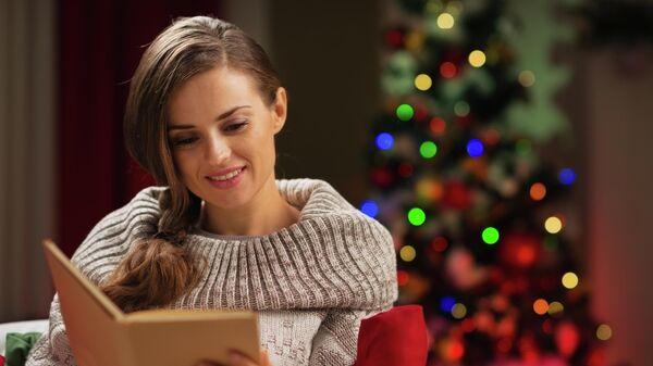 Девушка читает книгу у рождественской елки