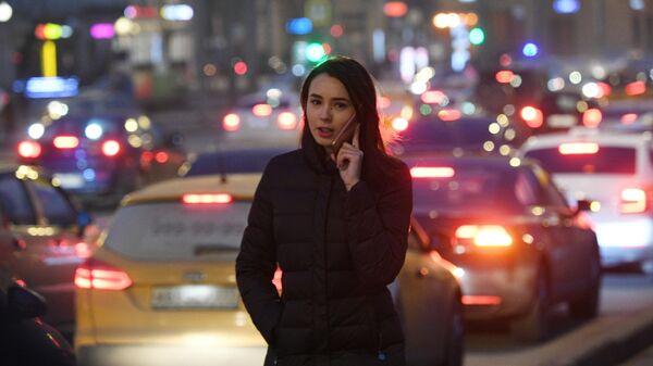 Девушка идет вдоль проезжей части  в Москве.