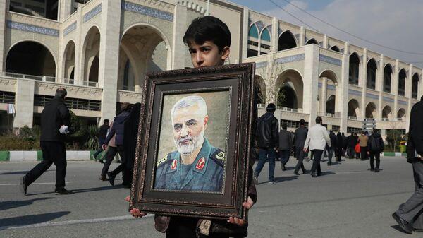 Мальчик несет портрет Касема Сулеймани, убитого во время авиаудара США в Ираке