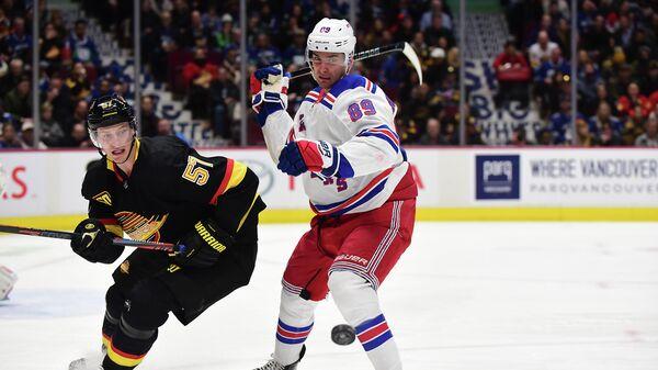 Игрок ХК Ванкувер Кэнакс Тайлер Майерс (57) и игрок ХК Нью-Йорк Рейнджерс Павел Бучневич  в матче регулярного чемпионата НХЛ