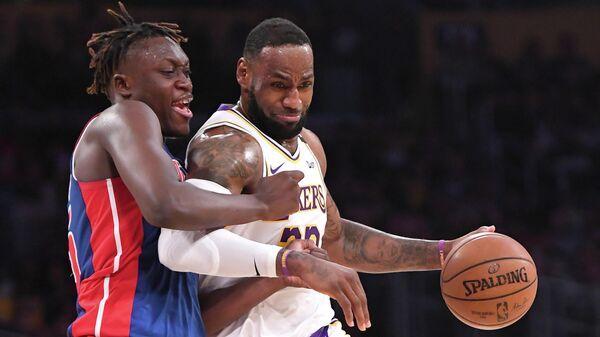 Игрок БК Детройт Пистонс Секу Думбуя (слева) и игрок БК Лос-Анджелес Лейкерс Леброн Джеймс в матче регулярного чемпионата НБА