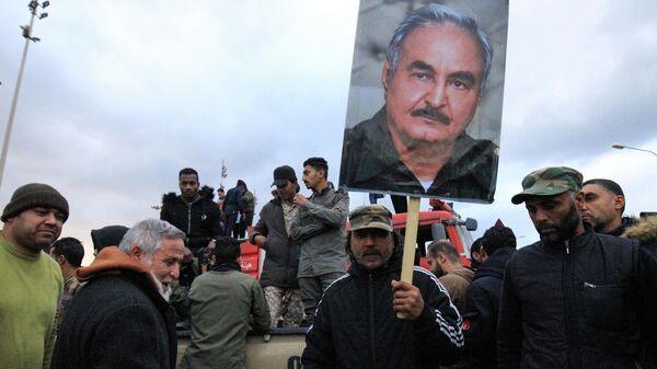 Люди с портретом генерала Халифы Хафтара во время демонстрации в Бенгази против вмешательства Турции и в поддержку признанного ООН правительства в Триполи