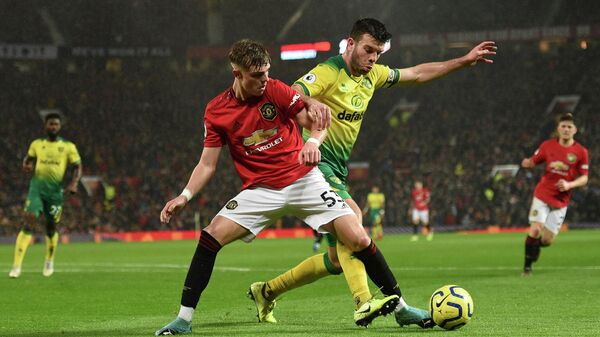 Norwich City's Scottish defender Grant Hanley (R) challenges Manchester United's English defender Brandon Williams (L) during the English Premier League football match between Manchester United and Norwich City at Old Trafford in Manchester, north west England, on January 11, 2020. (Photo by Oli SCARFF / AFP) / RESTRICTED TO EDITORIAL USE. No use with unauthorized audio, video, data, fixture lists, club/league logos or 'live' services. Online in-match use limited to 120 images. An additional 40 images may be used in extra time. No video emulation. Social media in-match use limited to 120 images. An additional 40 images may be used in extra time. No use in betting publications, games or single club/league/player publications. /