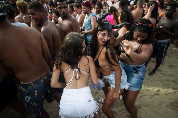 Женщины танцуют во время вечеринки Bloco da Favorita на пляже Копакабана в Рио-де-Жанейро, Бразилия