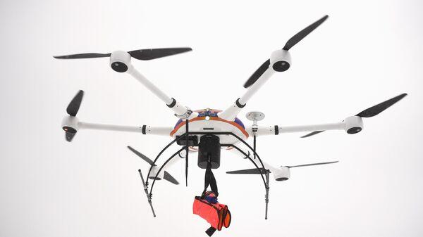 Беспилотный летательный аппарат с прикрепленным к нему спасательным жилетом во время отработки действий по ликвидации условных чрезвычайных ситуаций