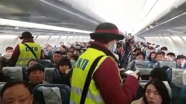 Сотрудники санитарно-карантинного пункта проводят дистанционную термометрию пассажиров на борту самолета, прибывшего в аэропорт Внуково