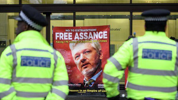 Офицеры полиции перед плакатом с фотографией Джулиана Ассанжа возле Вестминстерского мирового суда в Лондоне
