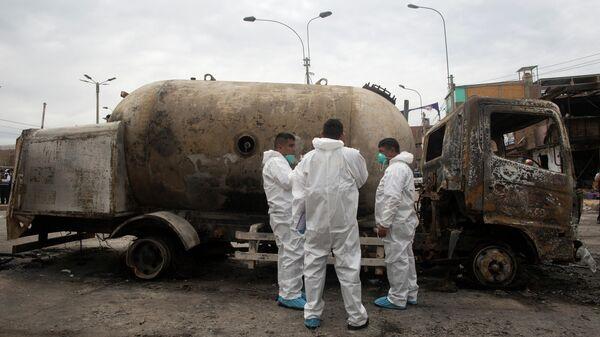 Следователи рядом с автоцистерной, перевозившейй газ, которая взорвалась в жилом районе в Лимы, Перу. 23 января 2020