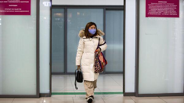 Пассажир в защитной маске в международном аэропорту Владивостока