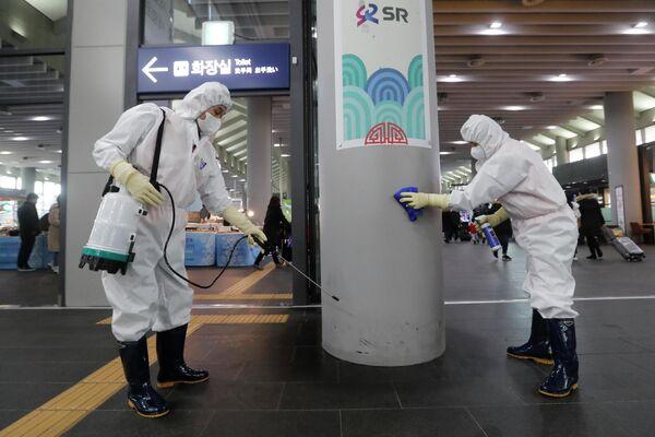Сотрудники чистят колонну на станции Сусео в Сеуле, Южная Корея