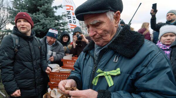 Житель блокадного Ленинграда пробует хлеб, изготовленный на хлебозаводе Ржевка-хлеб по рецепту 1941 года