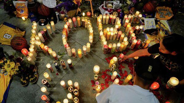Люди ставт свечки в память о Коби Брайанте