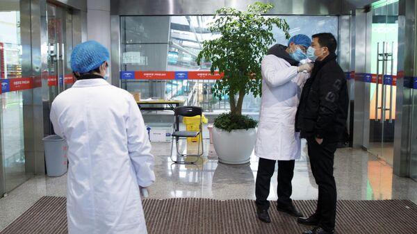 Медицинские работники измеряет температуру тела мужчины в зале вылета аэропорта в китайском городе Чанша