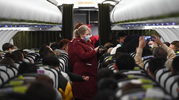 Сотрудники Роспотребназдора обследуют при помощи тепловизора пассажиров рейса авиакомпании S7, прибывшего из Пекина, в аэропорту Толмачево (Новосибирск)