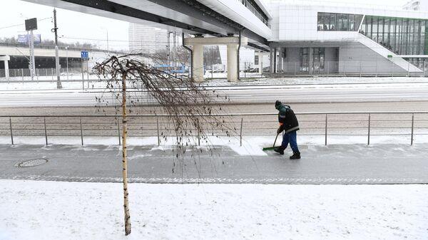 Сотрудник коммунальной службы чистит тротуар от снега в Москве