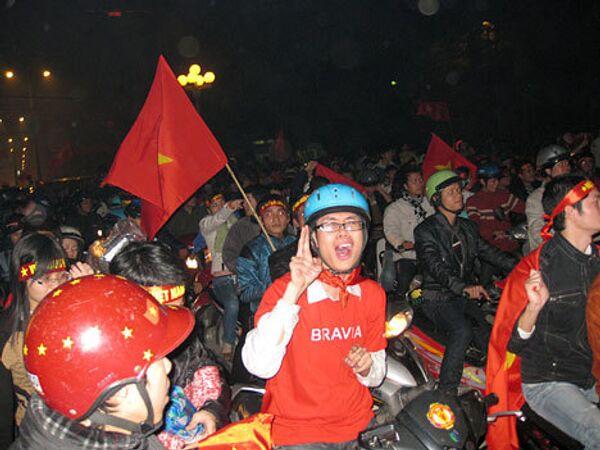 Вьетнамцы празднуют победу по футболу. Сборная команда страны впервые завоевал чемпионский титул
