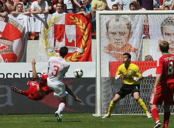 Защитник Локомотива Родольфо (справа) забивает мяч в ворота голкипера Спартака Сослана Джанаева