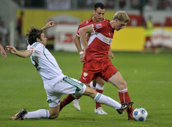 Защитник Вольфсбурга Андреа Барцальи (в белом) и нападающий Штутгарта Павел Погребняк (в красном)