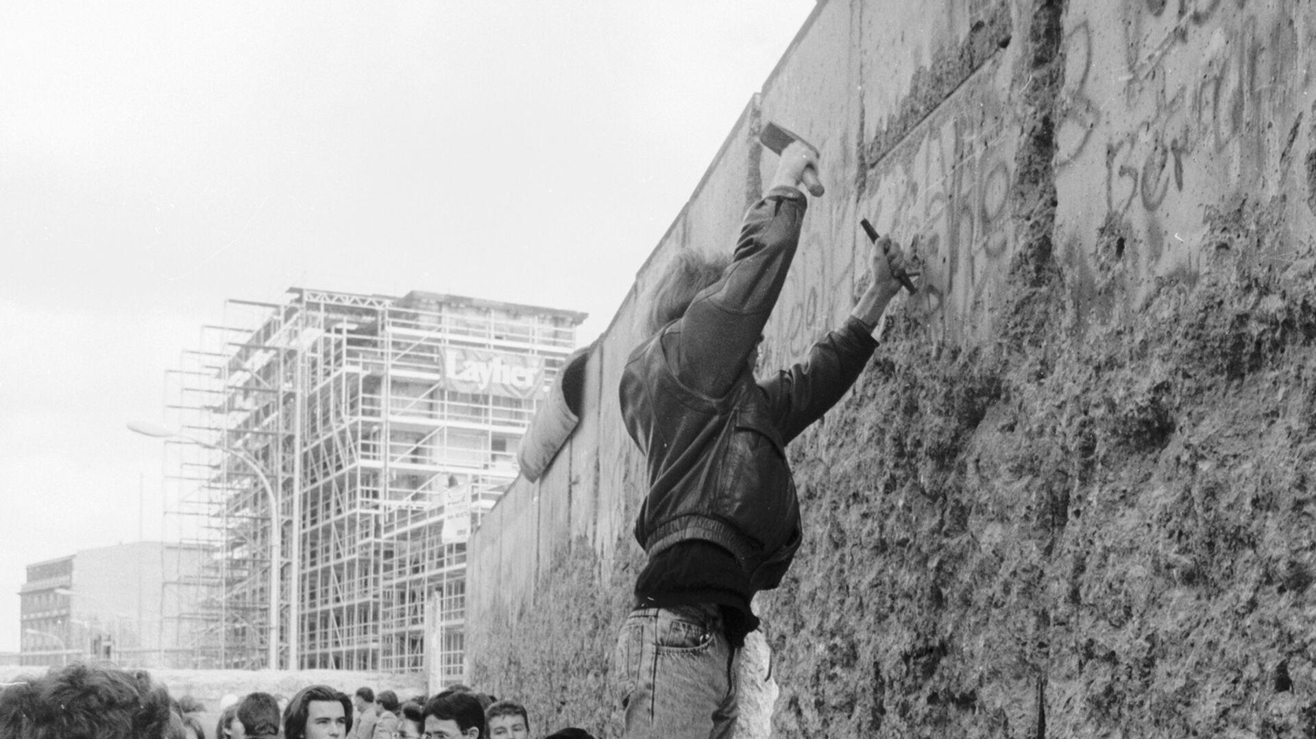 Житель Берлина отбивает кусок бетона от Берлинской стены - РИА Новости, 1920, 03.02.2021