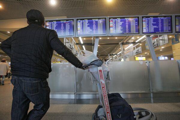 Пассажир у расписания вылета рейсов в здания аэровокзала Домодедово. Архив