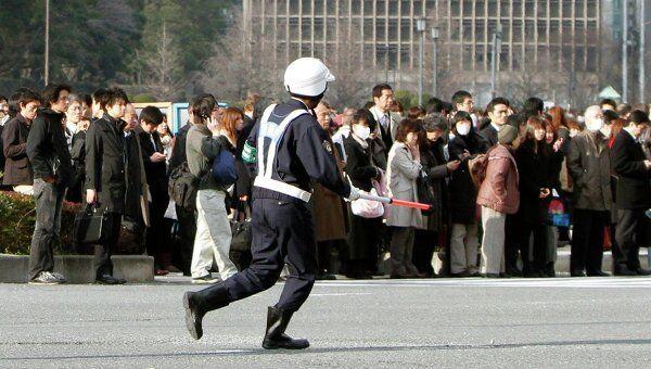 Люди эвакуированные из зданий в финансовом районе Токио после землетрясения 11 марта 2011