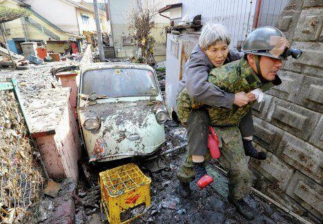 Солдаты сил самообороны Японии эвакуируют жителей из пострадавего от цунами города Kesennuma в префектуре Мияги на северо-востоке Японии, 12 марта 2011.