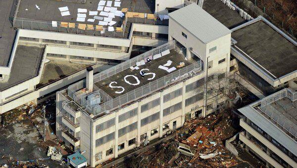 Люди ждут помощи на крыше здания после землетрясения в Kesennuma, префектура Мияги 12 марта 2011