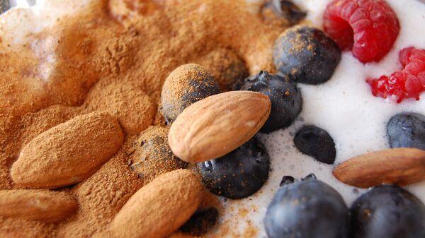 Добавьте в кефир орехи, корицу и ягоды, измельчите все в блендере - и сытный полезный завтрак готов!