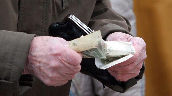 Пенсионер считает деньги. Архив