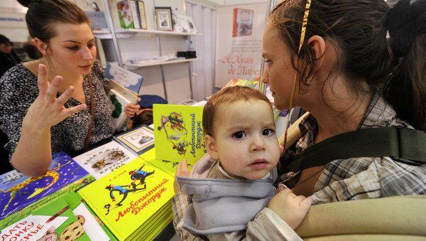 Посетительница с ребенком знакомится с книжными новинками для детей