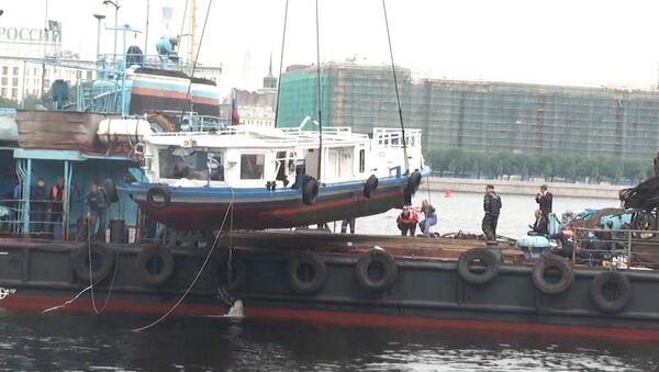 Поднятое со дна Невы затонувшее судно грузят на борт плавучего крана