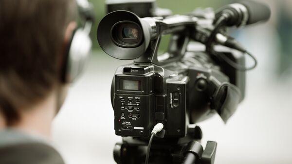 Журналист с видеокамерой. Архивное фото