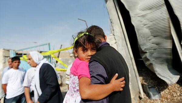 Мужчина держит на руках ребенка в приграничном уезде Акчакале на юго-востоке Турции