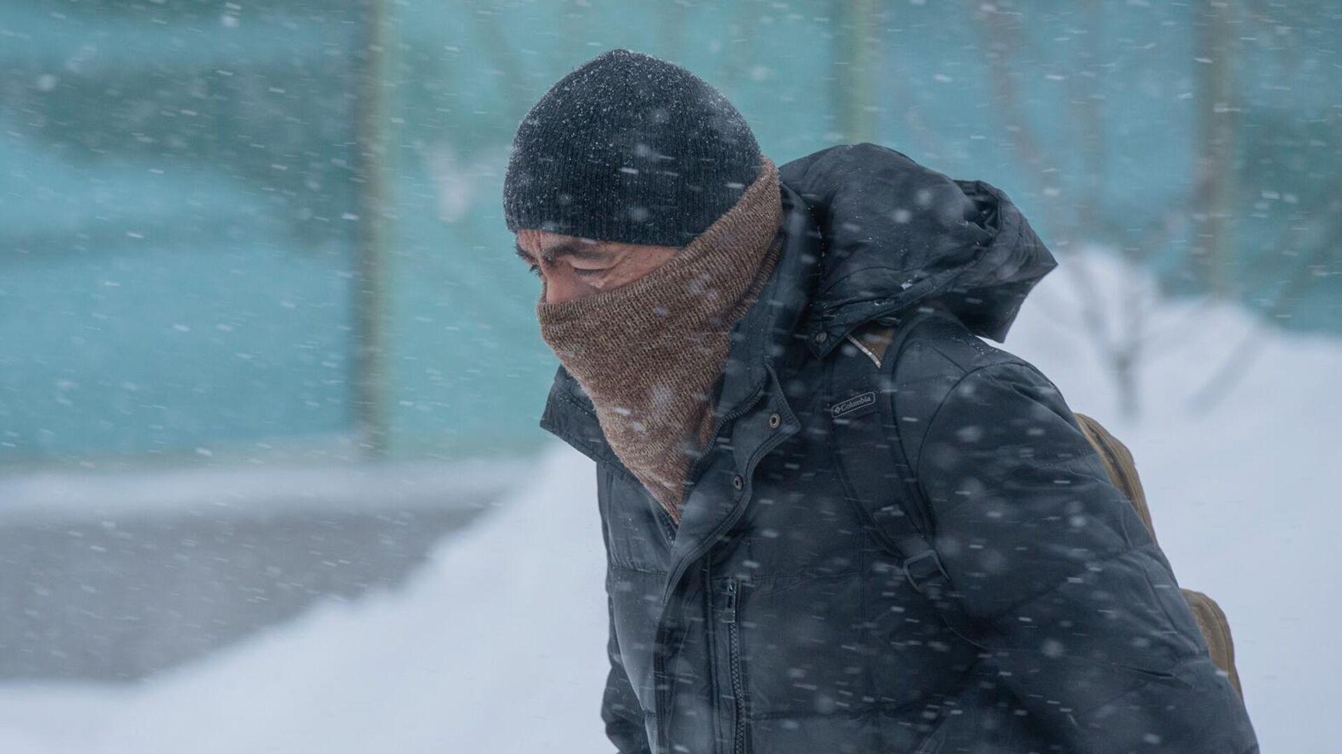 Мужчина идет по улице во время снежной метели в Нур-Султане. - РИА Новости, 1920, 24.12.2020