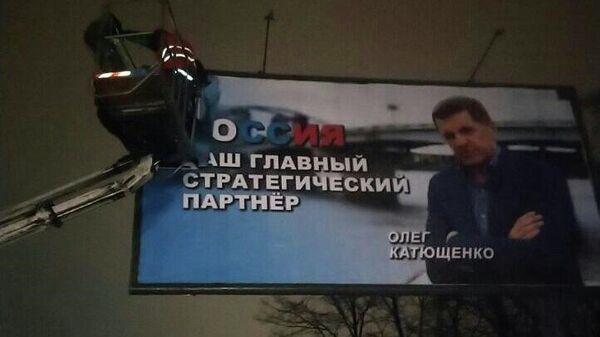 Работники коммунальных служб во время демонтажа в Киеве рекламного плаката с надписью Россия - наш главный стратегический партнер