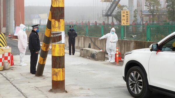 Медицинские работники в защитных костюмах на КПП в Китае
