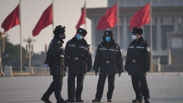 Полицейские в защитных масках на площади Тяньаньмэнь в Пекине