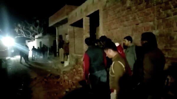 Местные жители и полицейские у здания, в котором мужчина удерживал заложников, в индийском штате Уттар-Прадеш. 30 января 2020