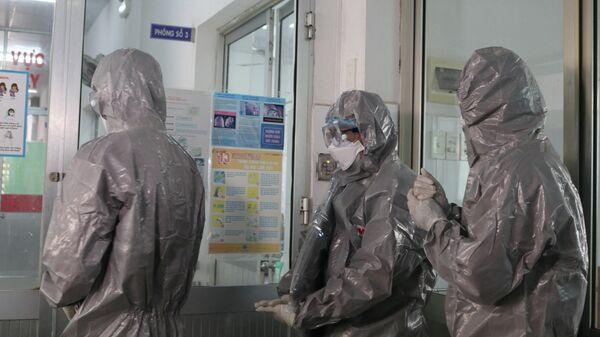 Врачи в защитных костюмах в больнице города Хошимин
