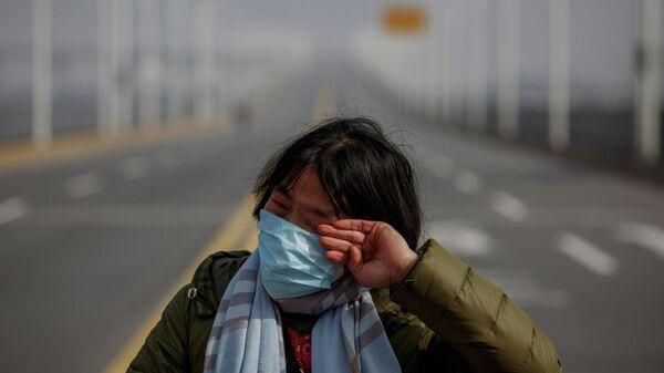 Женщина, прибывшая из провинции Хубэй, на контрольно-пропускном пункте на мосту через реку Янцзы в провинции Цзянси