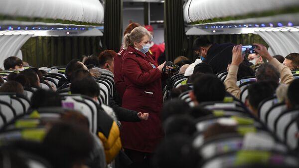 Сотрудники санитарно-карантинного пункта обследуют при помощи тепловизора пассажиров рейса авиакомпании S7 в аэропорту Толмачево