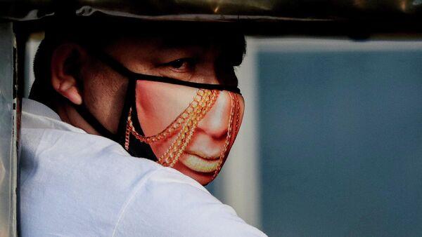 Мужчина в защитной маске с рисунком в Кесон-Сити, Филиппины