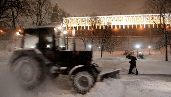 Сотрудник коммунальных служб убирает снег с помощью снегоуборочной техники