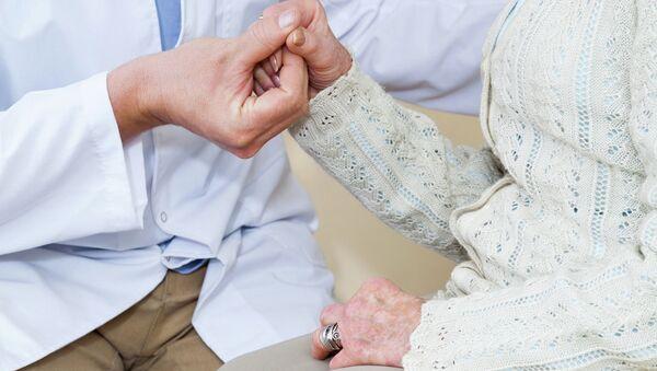 Врач держит пациентку за руку, архивное фото