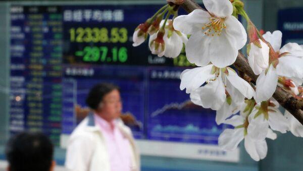 Цветущая сакура на фоне фондовой биржи в Токио. Архивное фото