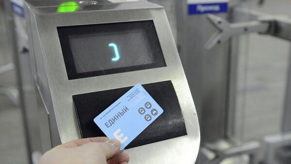 Пассажир прикладывает единый проездной билет к турникету на на станции Московского метрополитена. Архивное фото